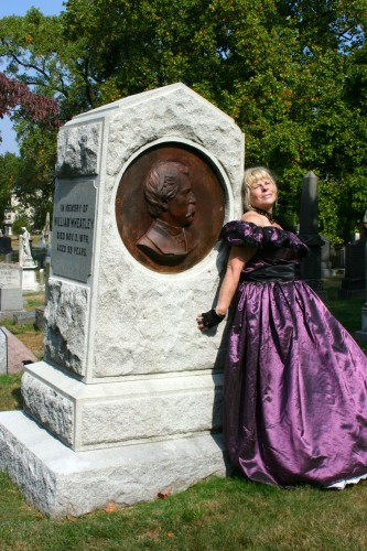 A dramatic pose by Marge Raymond at the grave of the producer of America's first musical.