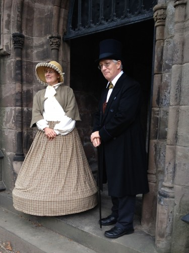 Mrs. and Dr. Mott (Stephanie and Mark Carey) await visitors at the threshold of their mausoleum.