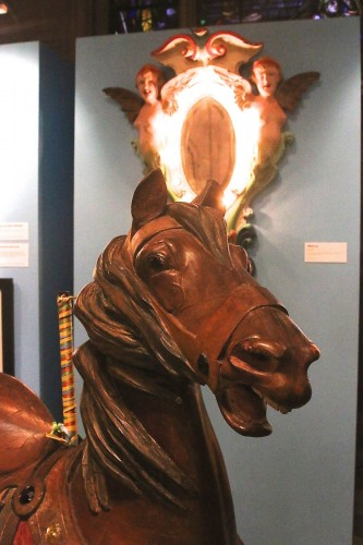 The Illions carousel horse, with its signature deeply-carved mane, and the Illions carousel decoration behind it.