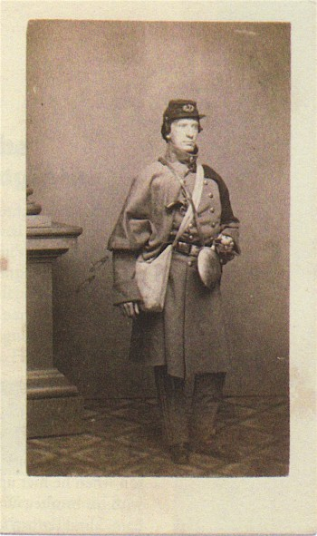 Surgeon Timothy Cheeseman, with a haversack slung over his shoulder, an uncovered canteen (standard in the 7th), a heavy overcoat, and a pistol, ready for a cold-weather march.