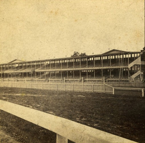 """Grand Stand, Front View."" Published by E. & H.T. Anthony & Co. A nicely composed photograph, with the track rail framing the grandstand."