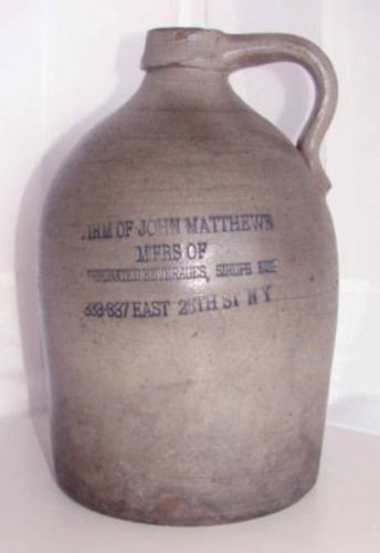 A stoneware crock with the label of the Matthews Company. These were used as containers for the various flavored syrups.