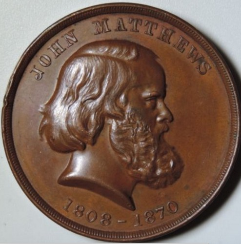 This promotional coin was issued by the John Matthews Company. It shows the face of the company's founder and his life dates. The Green-Wood Historic Fund Collections.