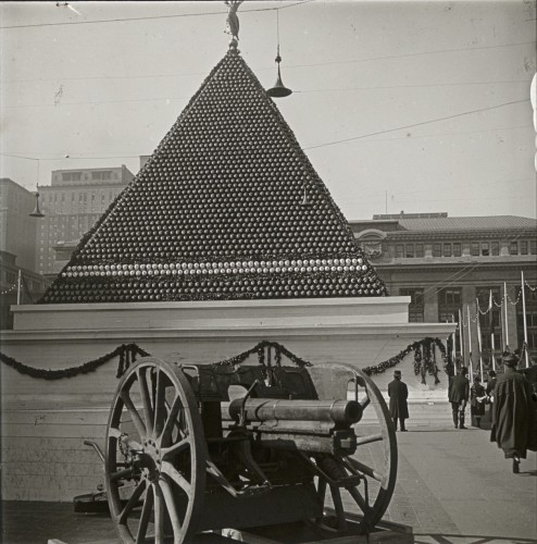 This is quite a visual--what appears to be a pyramid built of artillery shells, with a gun in the foreground.
