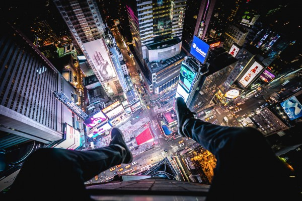 Christopher's signature set-up: his legs in the foreground, with a night scene of New York City below (in this case, high above Times Square).